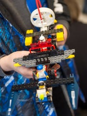 Silas Bowman, 10, holds a space ship he made out of