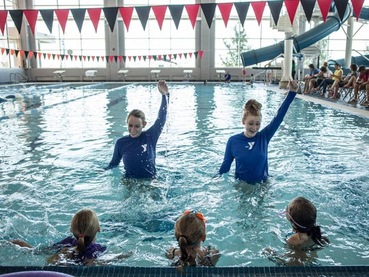 Instructors Savannah O'Neil, 19, and Aubrey Ruiz, 17, teach kids how to do a back stroke during a beginning swim class Thursday, June 23, 2016 at the YMCA of the Blue Water Area.