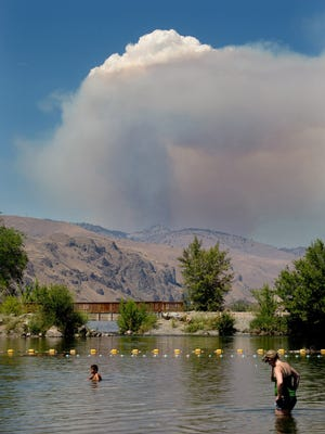 A plume of smoke and steam rises from the Mills Canyon Fire near Entiat, Wash., on Tuesday, July 8, 2014, as seen from Walla Walla Point Park and the Columbia Rive in Wenatchee. The fire is at 200 acres and growing according to Chelan County Emergency Management. (AP Photo/The Wenatchee World, Don Seabrook)
