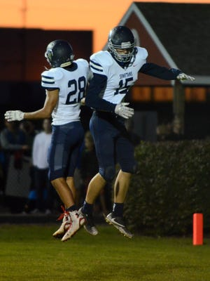 Brookfield East's Nick Pluemer (28) and Patrick Cartier celebrate Cartier's second touchdown catch of the night.