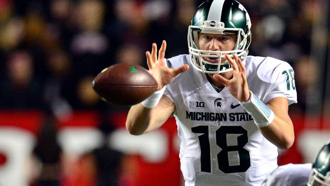 Michigan State quarterback Connor Cook takes a snap  as MSU plays Rutgers at High Point Solutions Stadium Saturday.