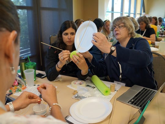 Dennie Glenn (right) works with other teachers to build a model of a wind turbine at the Honeywell Green Boot Camp sustainability workshop in San Diego.