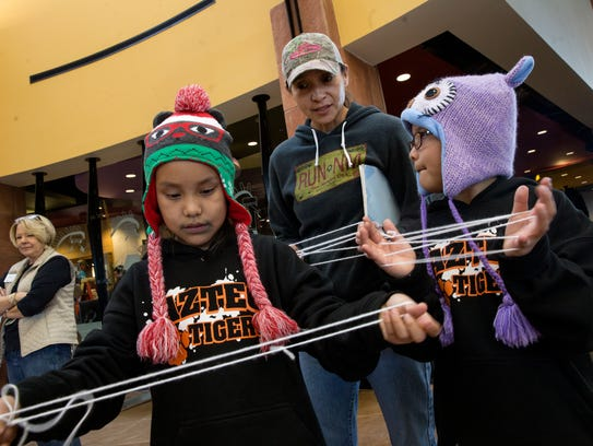 Sierrah Murphy, left, and her sister Aspen Murphy play a string game with their mother Michelle Murphy during the annual Winter Solstice Celebration on Thursday at the Farmington Public Library.