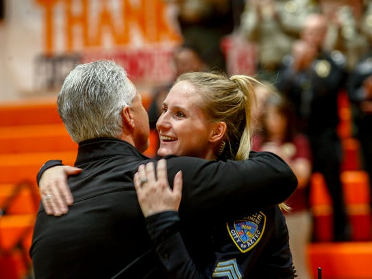 Aztec Superintendent Kirk Carpenter embraces Sgt. Heather Knibbs, a school resource officer with the Aztec Police Department, during a school assembly to honor first responders on Friday at Lily White Gym at Aztec High School.