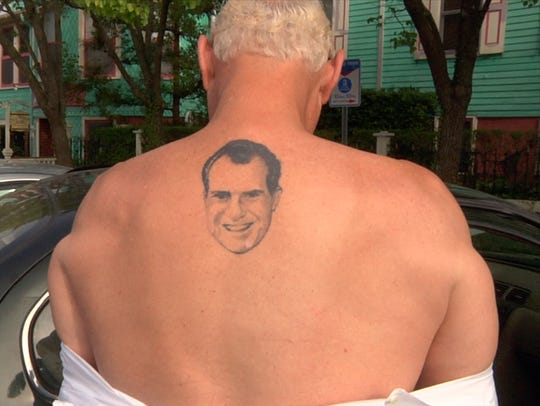 Roger Stone flashes his Richard Nixon tattoo in the
