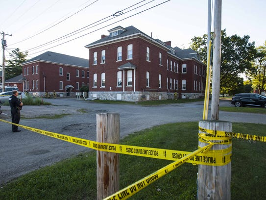 Police tape surrounds a building at the scene where