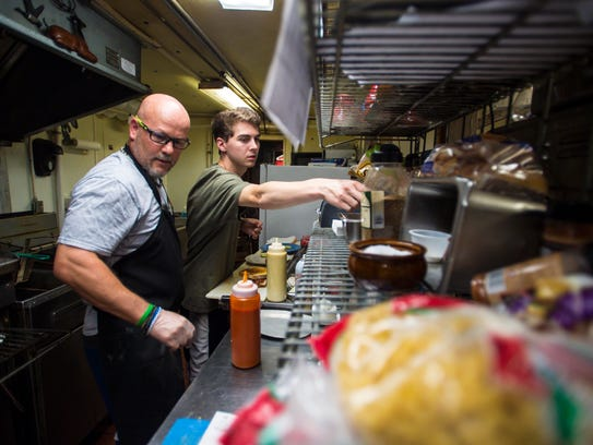 Jamie Rozzi, left, and Josh Mercure work in the kitchen