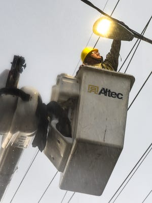 In this file photo, Guam Power Authority Line Repair Worker apprentice Shaun Taitano, works from the basket of a bucket truck during a downpour, as he checks an LED streetlight head for proper operation after its installation at Agana Heights.