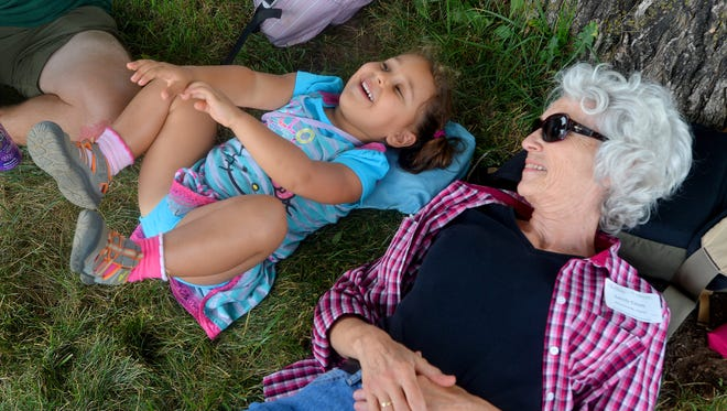 Maiara Dutra Elliott of Hawaii enjoys time with her grandmother, Sandy Elliott of Mechanicsville, as they relax under a tree during Field Dayat Polyface Farms in Swoope on July 19, 2014.