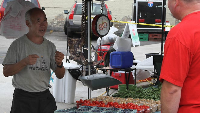 Bee Her from Her Farm in Kaukauna talks with a customer at his booth at the Oshkosh Farmer's Market on Saturday.