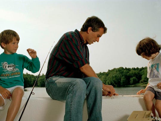 Robert Kennedy fishes with his son Bobby Jr., 8, left,