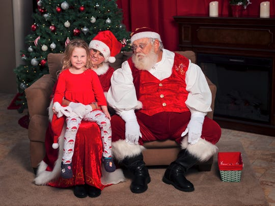 Kailyn Holdy, the 4-year old daughter of party hosts Tim and Brittany Holdy makes a Christmas wish with Mrs. and Santa Clause at her parents' Santa in The Pines benefit.
