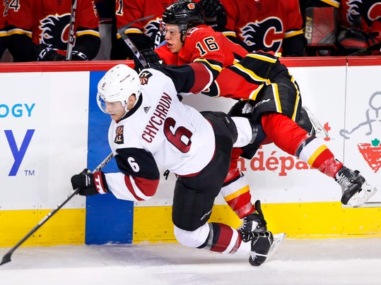 Arizona Coyotes'Jakob Chychrun (left) collides with Calgary Flames' Spencer Foo during first period NHL hockey action in Calgary, Alberta, Tuesday, April 3, 2018. (Larry MacDougal/The Canadian Press via AP)
