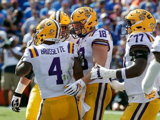 LSU players, including tight end Foster Moreau (18)