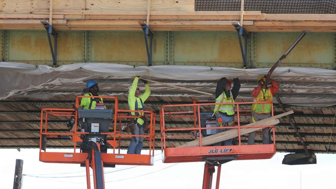 Workers nail plastic sheeting to the underside of the Ashford Avenue bridge in Ardsley, May 10, 2016. The $17.9 million dollar reconstruction project is expected to be completed by the Fall of 2018.