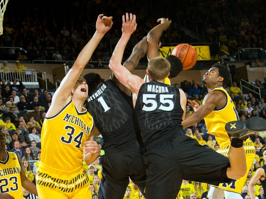 Michigan forward Mark Donnal (34) and guard Derrick Walton Jr., right, contests for a rebound with Xavier forward Jalen Reynolds (1) and guard J.P. Macura (55), in the first half of an NCAA college basketball game at Crisler Center in Ann Arbor, Mich., Friday, Nov. 20, 2015.