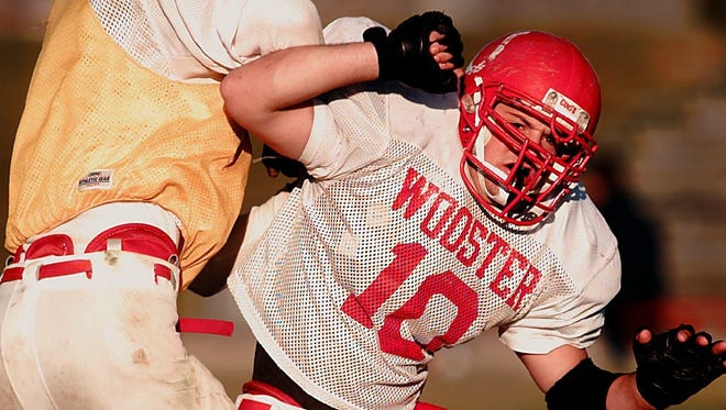 Wooster linebacker Bo Sellers rushes past an offensive lineman during a 1997 practice