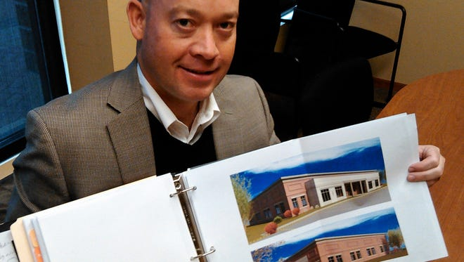 John Lohman displays artist renderings of his new building to be completed this June in North Liberty.