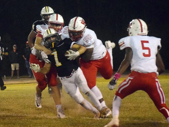 Winnfield defenders Eli Spangler (10, back left) and Rasheed Lyles (58, back right) wrap up Holy Savior Menard High School's Brandon Michot (7, center) Friday, Oct. 20, 2017.