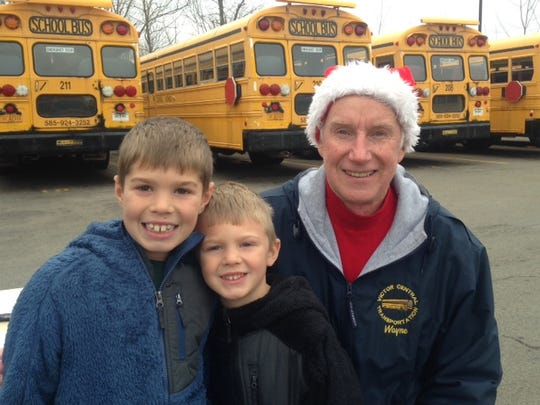 Brady Wortmann, 8, left, and Connor Wortmann, 5, of Farmington, with volunteer Wayne Brotsch.