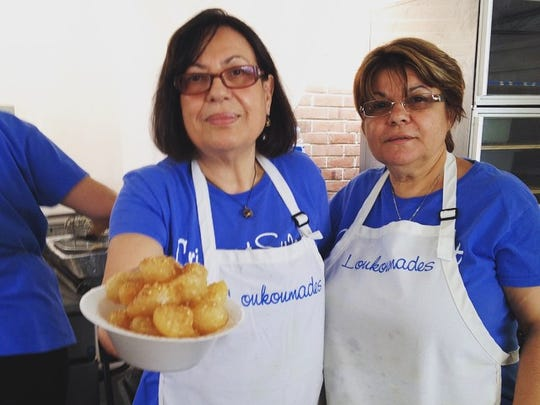 Loukomades is one of the most popular pastries at the St. George Greek Festival. Pictured are Eleni Lyssikatos, left, and  Despina Kounelias, both residents of Edison. Lyssikatos is among the parish families with three generations who volunteer at the festival. Her son, John, was its chairman for 15 years.