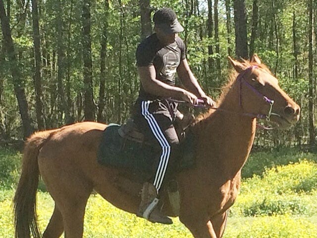 North DeSoto running back Delmonte Hall rides Brown Sugar, his Thoroughbred horse.