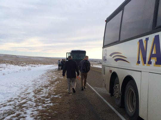 Nashua basketball players make their way to the Scobey bus after the Porcupines were stranded on the side of Montana Highway 13.