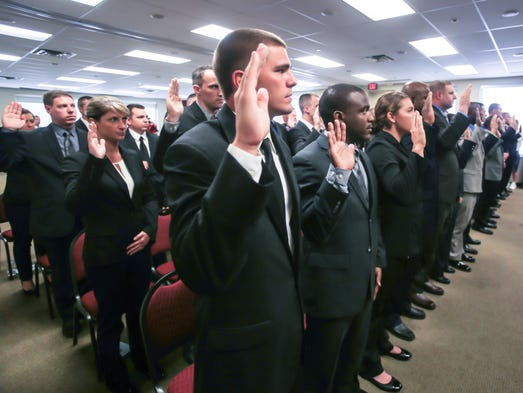 Monday June 2nd, 2014, recruits raise their right hands as recruits take the oath of office. City officials, IMPD leaders, and recruits gathered for the swearing in of the IMPD 9th Recruit Class, held at the Indianapolis Urban League.