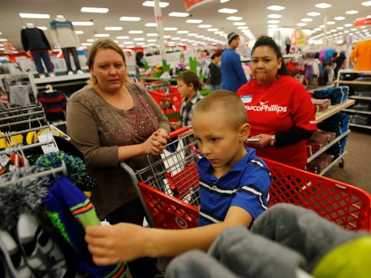 Amber Haddon, left, helps her son Daniel Haddon look for clothes with help from volunteer Tonya Bluehouse Wednesday at Target in Farmington.