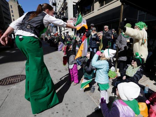 Frynnlee Shulda (from left), 6, Liko Johnson, 7, Brooklynn Hopp, 6, and  Autumn Hopp, 3, greet a stilt walker during the St. Patrick's Day Parade in downtown Milwaukee.