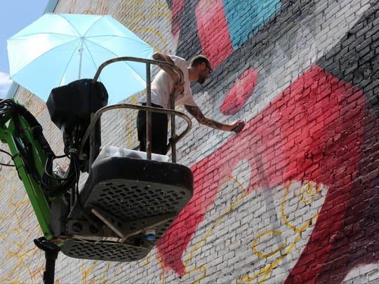 Eelco van den Berg, an artist from the Netherlands, is paining a mural on the side of a building on North Broadway in Yonkers.