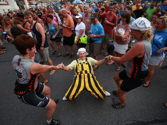 John Kirsch of Pine Valley, Iowa, gets a dance with Jessica Parker, left, of Fort Collins, Colorado, and Carrie Thatcher, right, of Broomfield, Colorado, as The Nadas perform a RAGBRAI concert on Thursday in Oskaloosa.