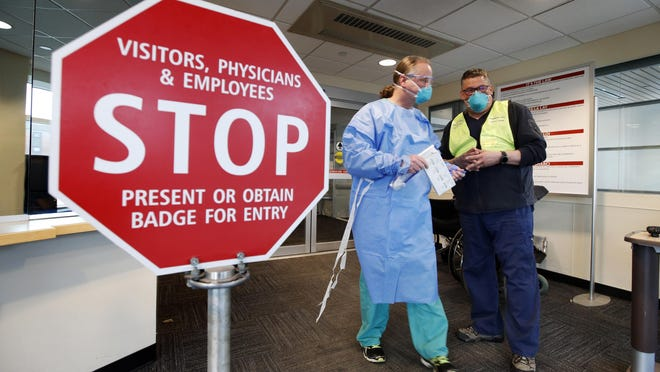 Medical personnel discuss patients that had been admitted for testing for the coronavirus at the entrance Central Maine Medical Center on Friday, March 13, 2020, in Lewiston, Maine.