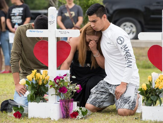 A woman becomes emotional at the makeshift memorial