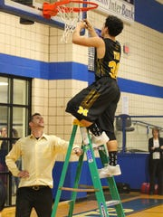 Menard High School head boys basketball coach Colby Rives smiles as Ethan Saucedo cuts down part of the net after beating Bronte in a Class 1A Region II regional quarterfinal at the Coleman gym on Tuesday, Feb. 27, 2018. Rives has guided Menard to the regional tournament in his first season as head coach.