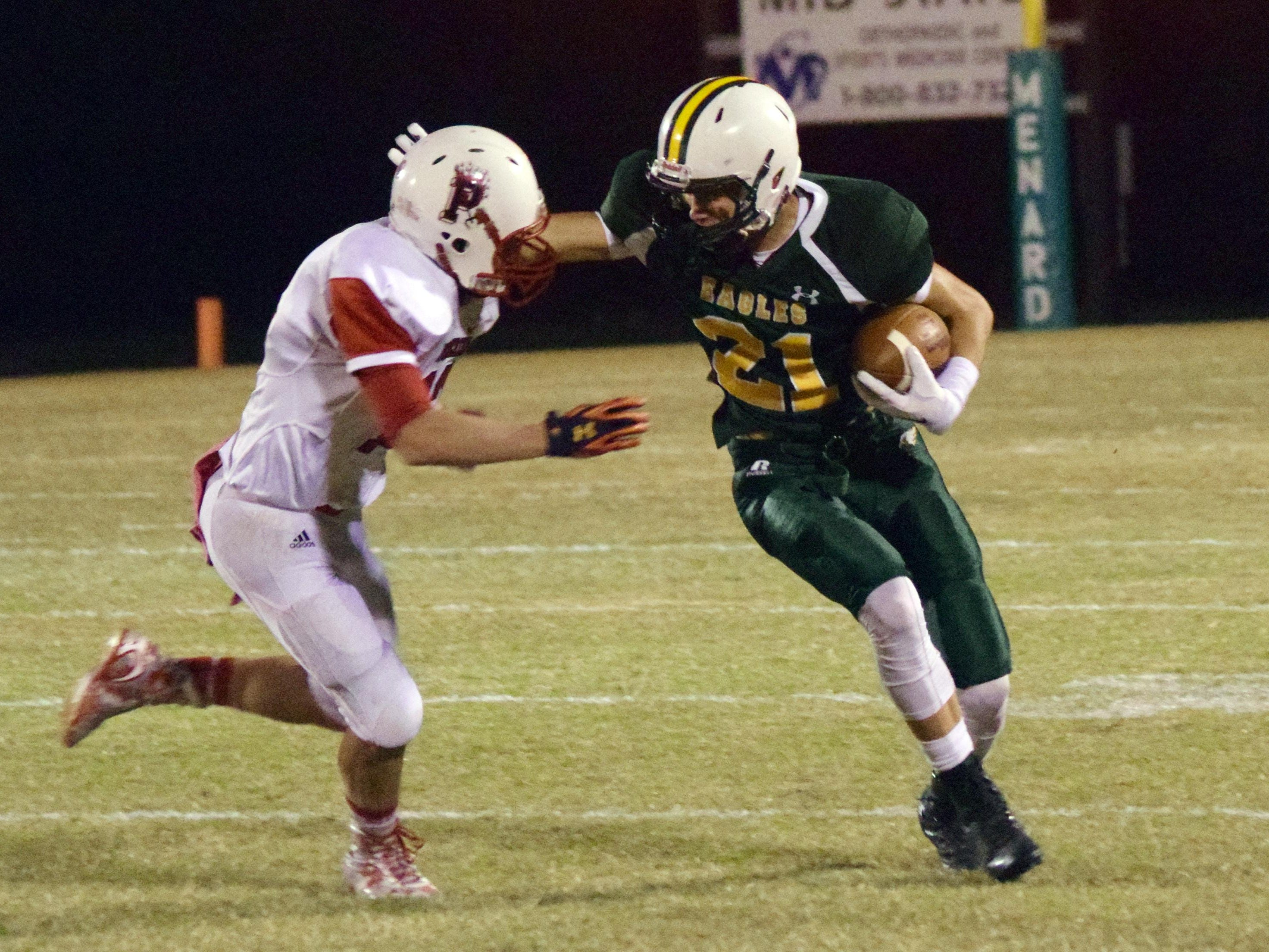 Menard's Adam Brown (21, right) delivers a stiff-arm to Pickering's Jordan Dowden (12, left) on Friday.