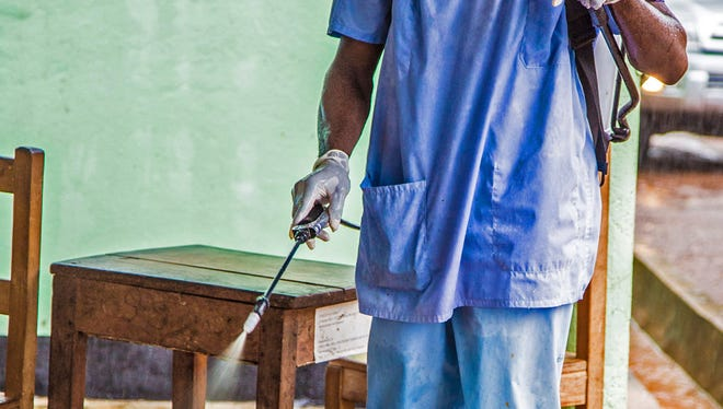 A health worker wearing a protective clothing spray disinfectant against the deadly Ebola virus at the Kenema Government Hospital in Kenema, 300 kilometers, (186 miles) from the capital city of Freetown, Sierra Leone.  Over the decades, Ebola cases have been confirmed in 10 African countries, including Congo where the disease was first reported in 1976. But until this year, Ebola had never come to West Africa.