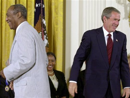 FILE - In this July 9, 2002 file photo, President George W. Bush lets out a laugh after failing to get the clasp together on Bill Cosby's Presidential Medal of Freedom, which he holds, after Bush tried to put on the entertainer, in the East Room of the White House in Washington. President Barack Obama is rejecting the idea of revoking Cosby's Presidential Medal of Freedom because of sexual misconduct allegations. Obama says there's no precedent or mechanism to take back the medal. He declined to talk about the specific allegations against Cosby because there are pending legal matters.