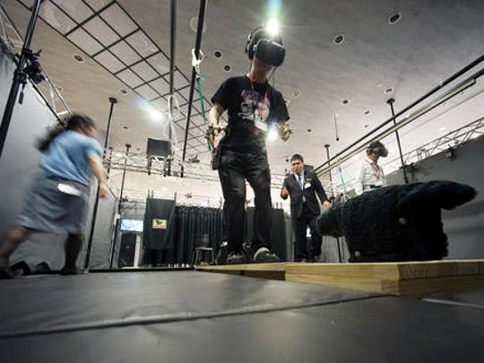 "In this May 31, 2016 photo, a visitor, wearing a U.S. maker HTC's Vive headset, plays ""Fear of Heights Show"" to rescue a mewling cat perched on a wooden plank that balances from the edge of a skyscraper at the ""VR Zone Project i Can"" virtual reality experimental  entertainment facility in Tokyo. The cat rescue is one of eight VR experiences created by game-maker Bandai Namco for HTC's Vive headset. Another entails shooting flying robotic spaceships with a manga-like female character as your co-pilot."