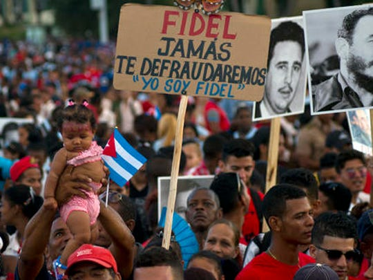 People waits for the beginning of a rally honoring Cuba's leader Fidel Castro before his burial Sunday at the Plaza Antonio Maceo in Santiago, Cuba, Saturday, Dec. 3, 2016. The sign reads in Spanish 'Fidel we will never let you down. I am Fidel.'