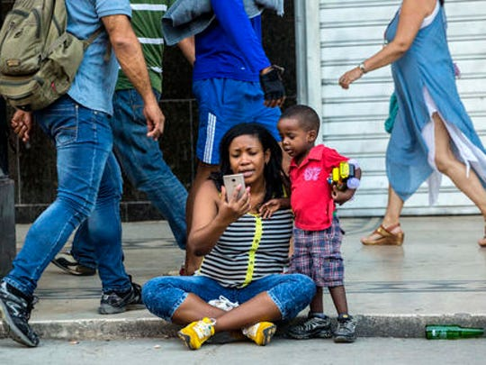 In this Jan. 6, 2017 photo a woman with her child uses a public wifi hotspot in Havana, Cuba. While the island nation remains one of the world's least internet-connected societies, ordinary citizens' access to the internet has exploded over the last two years.