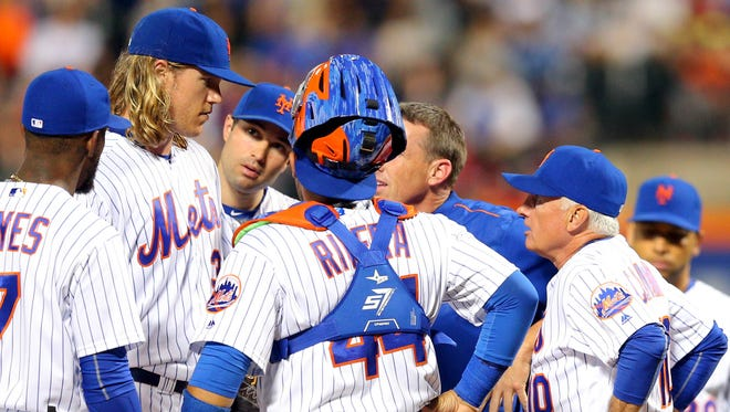 Noah Syndergaard talks with Mets manager Terry Collins right, and a trainer during the fifth inning against the Nationals at Citi Field.