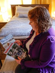 """Marsha McCormack has been renting out a room in her home on Altam Avenue in Carmel, Ind., ever since the 100th running of the Indianapolis 500. """"I just couldn't stand to watch people get scammed,"""" she said. """"I charged $69 a night."""" Here, she shuffles through reading material she leaves inside the room she used to be able to rent out on Airbnb on Friday, Jan. 20, 2017."""