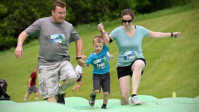 Scott Mattfield and his wife Crystal, Bemidji, hold hands with their son Isaac as they run over and obstacle during the Insane Inflatable 5K.