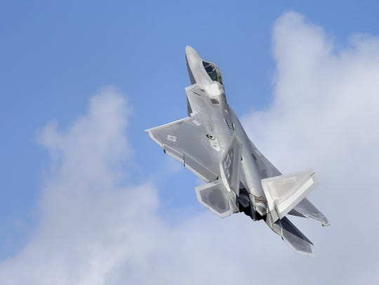 A F-22 Raptor takes off through the sky over EAA AirVenture