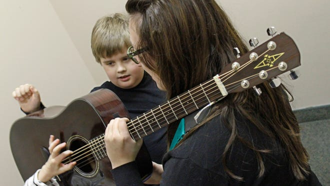 """Music therapist Megan Smith holds up her guitar as she plays a game of """"Knock, Knock, Knock"""" with Andrew Vaden, 8, Webster, in their art music class at the Family Autism Center."""