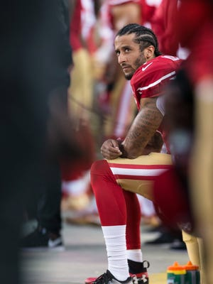 Colin Kaepernick sits during the national anthem.