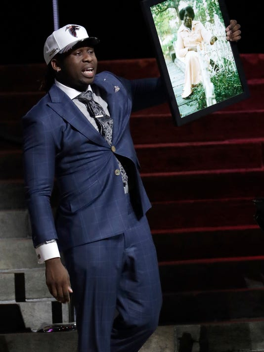 UCLA's Takkarist McKinley carries a photograph of his grandmother onstage after being selected by the Atlanta Falcons during the first round of the 2017 NFL football draft, Thursday, April 27, 2017, in Philadelphia. (AP Photo/Julio Cortez)