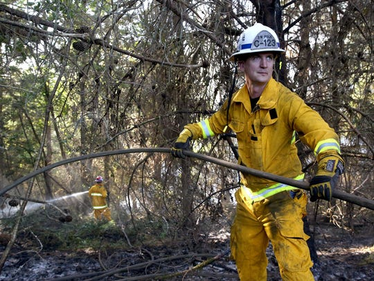 Shane Castle, of the Falls City Fire Department, mops up a blaze Friday west of Monmouth.