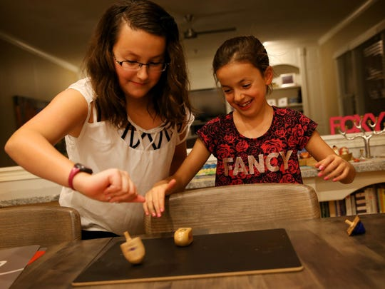 Hailey, 12, and Avery Fox, 8, spin their dreidels on Dec. 4, 2015, during their family's annual celebration of Hanukkah.